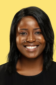 Jovem mulher afro-americana isolada no fundo amarelo do estúdio, expressão facial. linda mulher fechar retrato. conceito de emoções humanas, expressão facial. sorrindo, mantendo a calma.