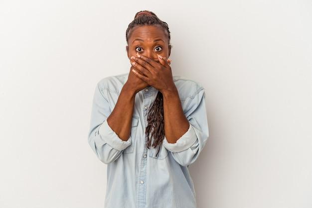 Jovem mulher afro-americana isolada no fundo branco, cobrindo a boca com as mãos parecendo preocupadas.