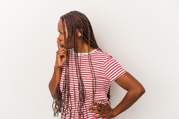 Jovem mulher afro-americana, isolada no fundo branco, mantendo um segredo ou pedindo silêncio.