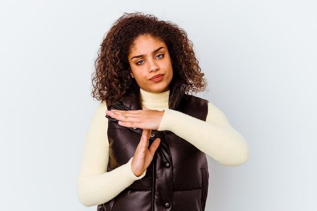 Jovem mulher afro-americana isolada no fundo branco, mostrando um gesto de tempo limite.