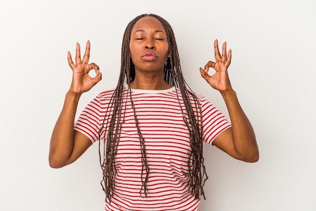 Jovem mulher afro-americana isolada no fundo branco relaxa após um árduo dia de trabalho, ela está realizando ioga.
