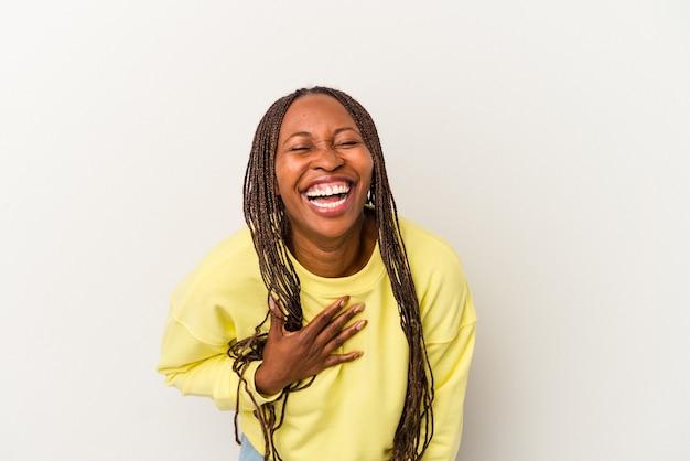 Jovem mulher afro-americana, isolada no fundo branco, ri alto, mantendo a mão no peito.