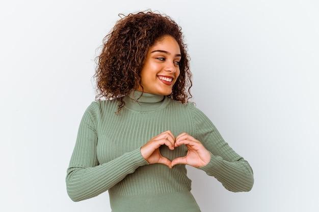 Jovem mulher afro-americana isolada no fundo branco, sorrindo e mostrando uma forma de coração com as mãos.