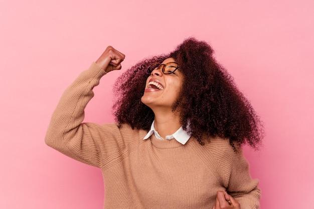 Jovem mulher afro-americana isolada no fundo rosa, levantando o punho após uma vitória, o conceito de vencedor.