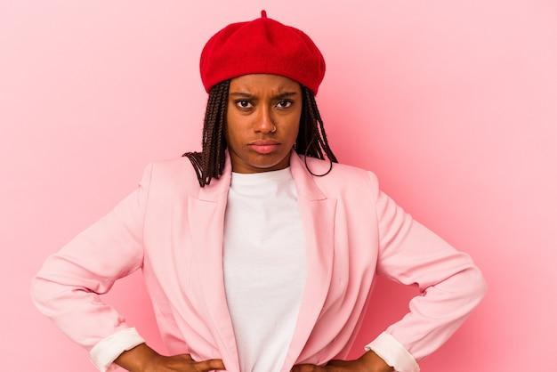 Jovem mulher afro-americana isolada no fundo rosa rosto triste, sério, sentindo-se miserável e descontente.