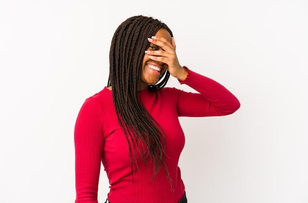 Jovem mulher afro-americana isolada piscar para a câmera através dos dedos, rosto de vergonha coberta.