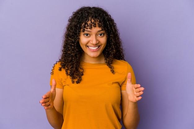 Jovem mulher afro-americana isolada segurando algo com as duas mãos, apresentação do produto.
