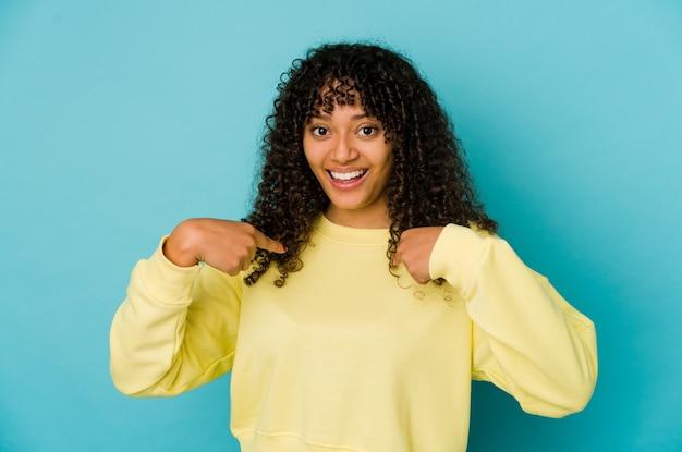 Jovem mulher afro-americana isolada surpresa apontando com o dedo, sorrindo amplamente.