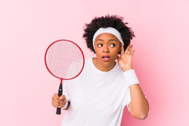 Jovem mulher afro-americana jogando badminton isolado, tentando ouvir uma fofoca.