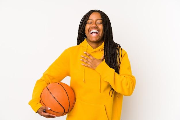 Jovem mulher afro-americana jogando basquete isolado ri alto, mantendo a mão no peito.