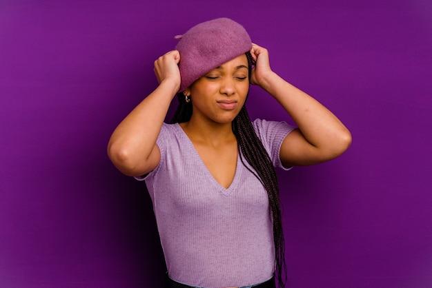 Jovem mulher afro-americana jovem mulher afro-americana, cobrindo as orelhas com as mãos.