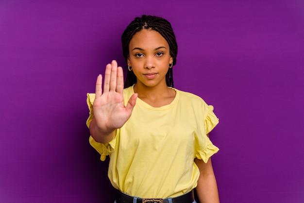 Jovem mulher afro-americana jovem mulher afro-americana em pé com a mão estendida, mostrando o sinal de stop, impedindo você.