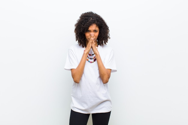 Jovem mulher afro-americana legal se sentindo preocupada, esperançosa e religiosa, orando fielmente com as palmas das mãos pressionadas, pedindo perdão