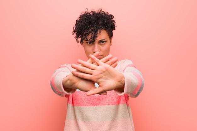Jovem mulher afro-americana mista adolescente fazendo um gesto de negação