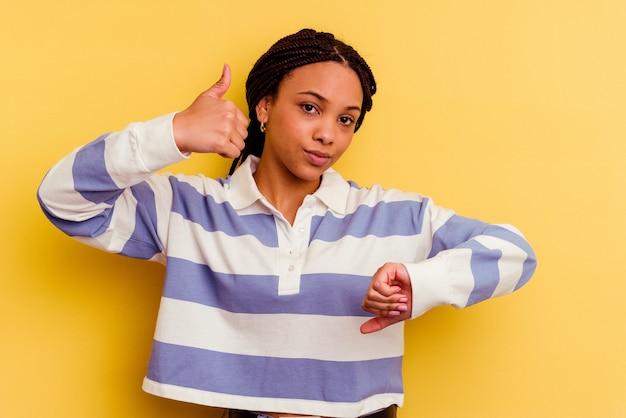 Jovem mulher afro-americana mostrando os polegares para cima e para baixo, difícil escolher o conceito
