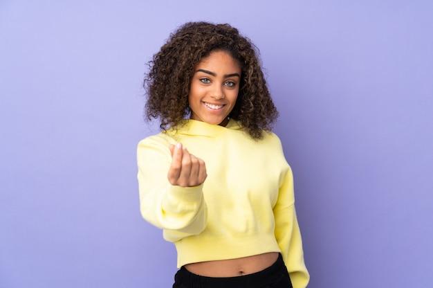 Jovem mulher afro-americana na parede fazendo dinheiro gesto
