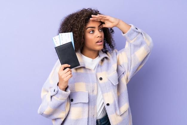 Jovem mulher afro-americana na parede roxa em férias com bilhetes de avião e passaporte enquanto olha algo à distância