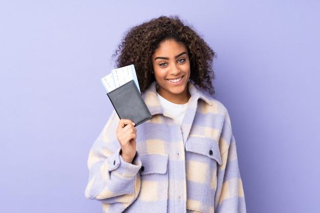 Jovem mulher afro-americana na parede roxa feliz em férias com bilhetes de avião e passaporte