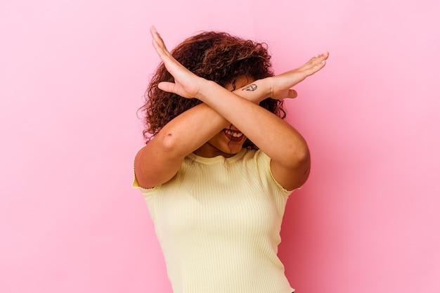 Jovem mulher afro-americana na rosa, mantendo os dois braços cruzados, conceito de negação.