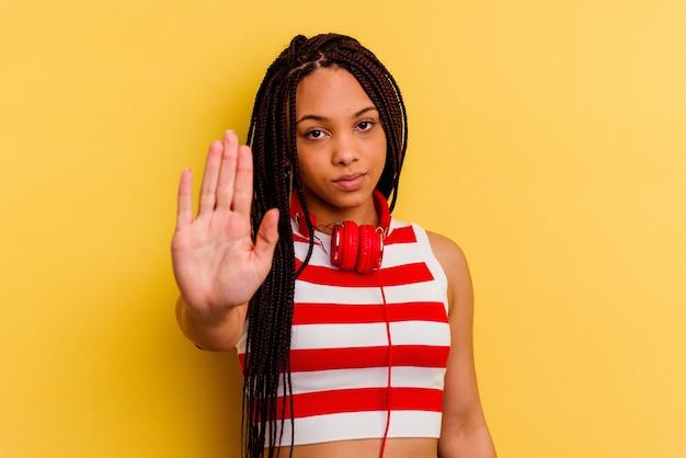 Jovem mulher afro-americana, ouvindo música com fones de ouvido isolados na parede amarela em pé com a mão estendida, mostrando o sinal de pare, impedindo você.