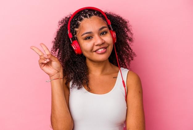 Jovem mulher afro-americana, ouvindo música com fones de ouvido isolados no fundo rosa, alegre e despreocupada, mostrando um símbolo de paz com os dedos.