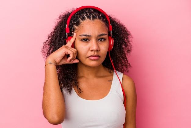 Jovem mulher afro-americana, ouvindo música com fones de ouvido isolados no fundo rosa, apontando o templo com o dedo, pensando, focado em uma tarefa.