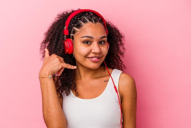 Jovem mulher afro-americana ouvindo música com fones de ouvido isolados no fundo rosa, mostrando um gesto de chamada de celular com os dedos.