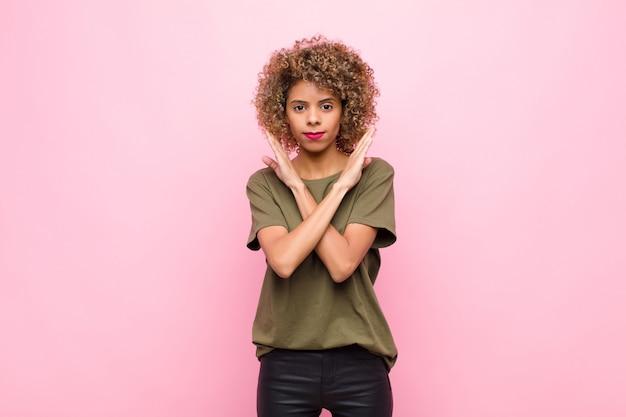 Jovem mulher afro-americana parecendo irritada e cansada de sua atitude, dizendo o suficiente! mãos cruzadas na frente, dizendo para você parar na parede rosa