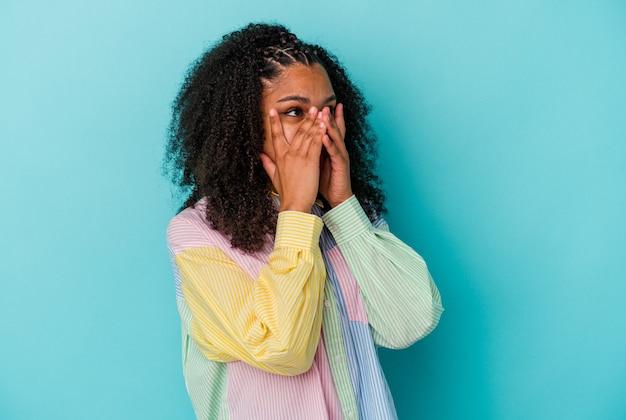 Jovem mulher afro-americana pisca por entre os dedos assustada e nervosa.