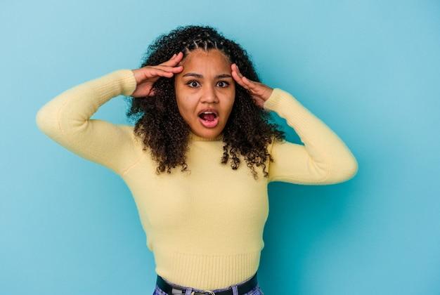 Jovem mulher afro-americana, recebendo uma agradável surpresa, animada e levantando as mãos.
