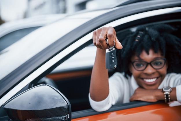 Jovem mulher afro-americana se senta dentro de um carro novo e moderno com as chaves na mão.