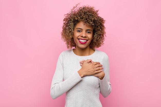 Jovem mulher afro-americana se sentindo romântica, feliz e apaixonada, sorrindo alegremente e segurando as mãos perto do coração na parede rosa