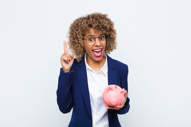 Jovem mulher afro-americana se sentindo um gênio feliz e animado depois de realizar uma ideia, levantando o dedo alegremente, eureka! com um cofrinho