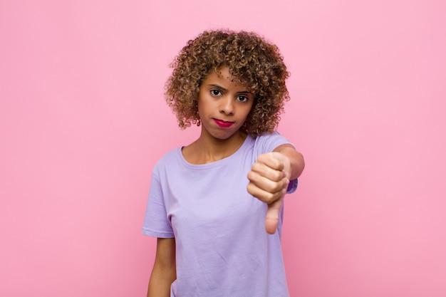 Jovem mulher afro-americana se sentindo zangada, irritada, irritada, decepcionada ou descontente, mostrando o polegar para baixo com um olhar sério na parede rosa