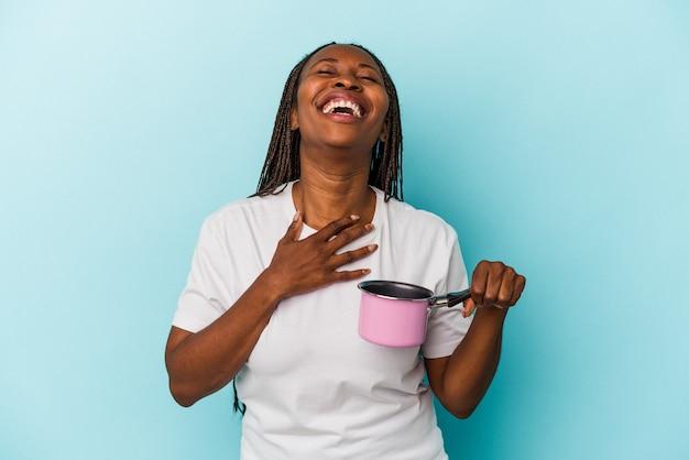 Jovem mulher afro-americana, segurando a panela isolada sobre fundo azul, ri alto, mantendo a mão no peito.