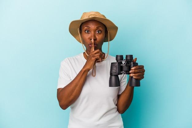 Jovem mulher afro-americana segurando binóculos isolados em um fundo azul, mantendo um segredo ou pedindo silêncio.