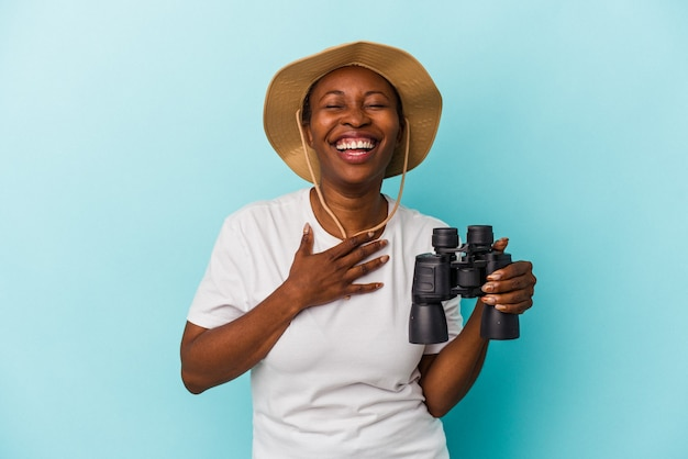 Jovem mulher afro-americana segurando binóculos isolados sobre fundo azul ri alto, mantendo a mão no peito.