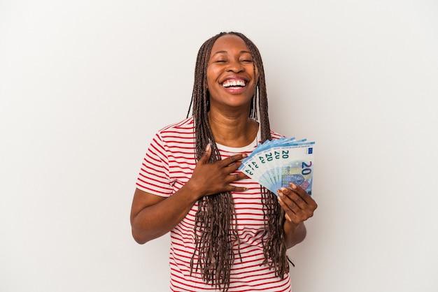 Jovem mulher afro-americana segurando notas isoladas no fundo branco ri alto, mantendo a mão no peito.