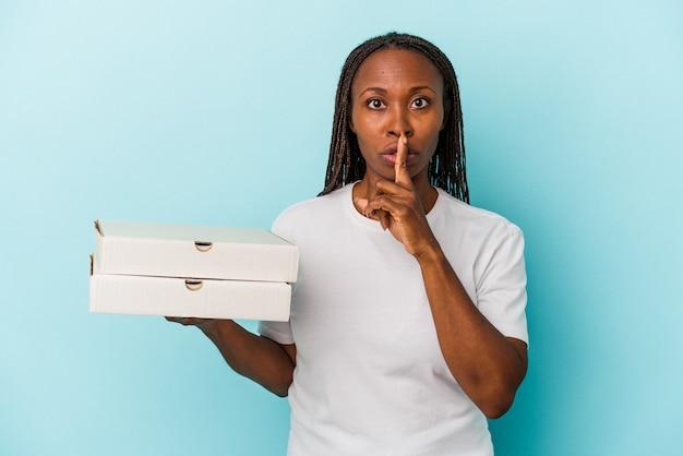 Jovem mulher afro-americana segurando pizzas isoladas em um fundo azul, mantendo um segredo ou pedindo silêncio.