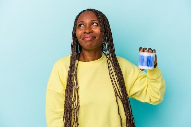 Jovem mulher afro-americana segurando touros de algodão isolados no fundo dos botões sonhando em alcançar objetivos e propósitos