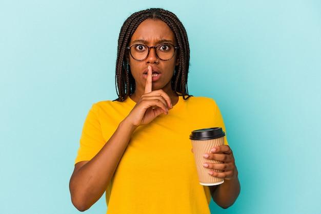 Jovem mulher afro-americana segurando um café para levar isolado sobre fundo azul, mantendo um segredo ou pedindo silêncio.