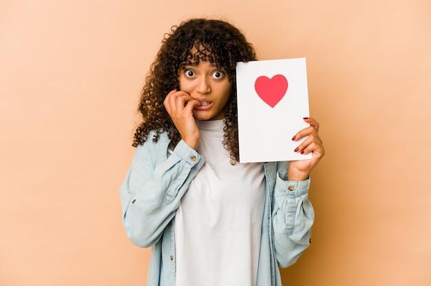 Jovem mulher afro-americana segurando um cartão de dia dos namorados, roendo as unhas, nervosa e muito ansiosa.