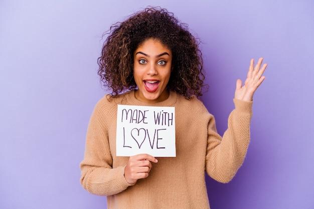 Jovem mulher afro-americana segurando um cartaz feito com amor, isolado no fundo roxo, recebendo uma agradável surpresa, animada e levantando as mãos.