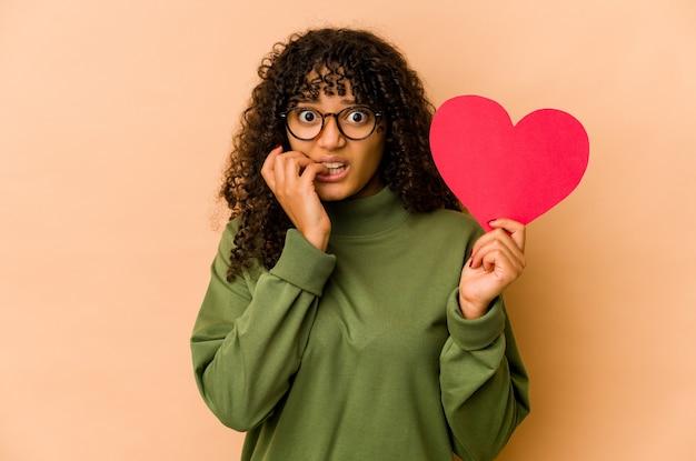 Jovem mulher afro-americana segurando um coração de dia dos namorados, roendo as unhas, nervosa e muito ansiosa.