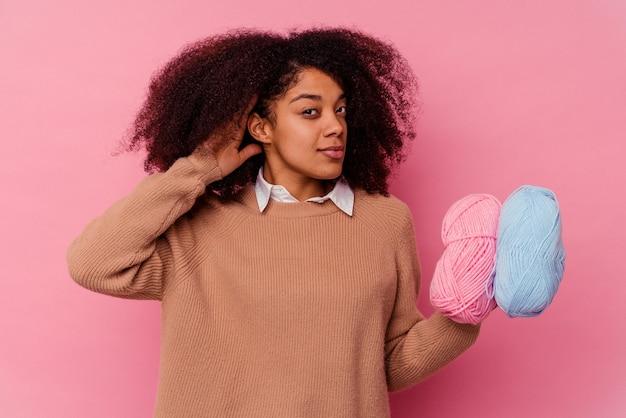Jovem mulher afro-americana segurando um fio de costura isolado no fundo rosa, tentando ouvir uma fofoca.