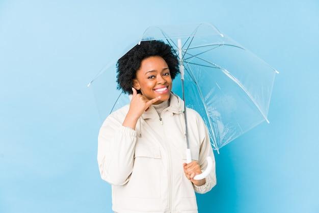 Jovem mulher afro-americana segurando um guarda-chuva isolado, mostrando um gesto de chamada de celular com os dedos.