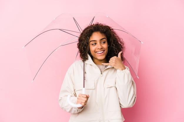 Jovem mulher afro-americana segurando um guarda-chuva, mostrando um gesto de chamada de celular com os dedos.