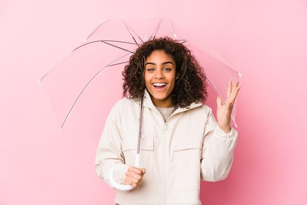 Jovem mulher afro-americana segurando um guarda-chuva, recebendo uma agradável surpresa, animada e levantando as mãos.