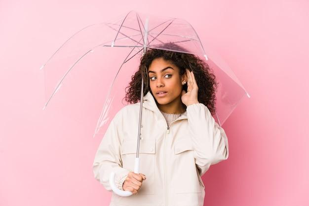 Jovem mulher afro-americana segurando um guarda-chuva, tentando ouvir uma fofoca.
