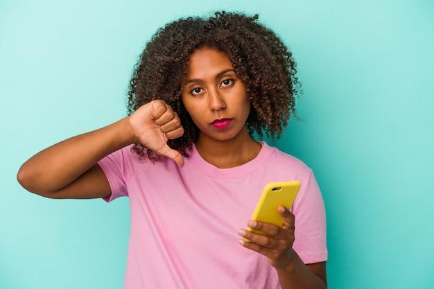Jovem mulher afro-americana segurando um telefone móvel isolado em um fundo azul, mostrando um gesto de antipatia, polegares para baixo. conceito de desacordo.